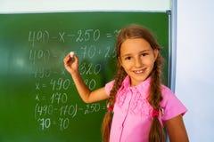 Χαμογελώντας κορίτσι με τις πλεξούδες και κιμωλία κοντά στον πίνακα Στοκ Φωτογραφίες