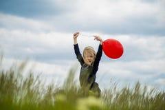 Χαμογελώντας κορίτσι με το κόκκινο μπαλόνι Στοκ φωτογραφία με δικαίωμα ελεύθερης χρήσης