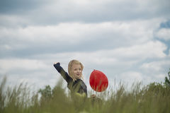 Χαμογελώντας κορίτσι με το κόκκινο μπαλόνι Στοκ εικόνα με δικαίωμα ελεύθερης χρήσης