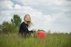 Χαμογελώντας κορίτσι με το κόκκινο μπαλόνι Στοκ Φωτογραφία