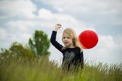 Χαμογελώντας κορίτσι με το κόκκινο μπαλόνι Στοκ Φωτογραφίες