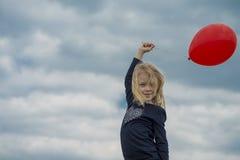 Χαμογελώντας κορίτσι με το κόκκινο μπαλόνι Στοκ Εικόνες