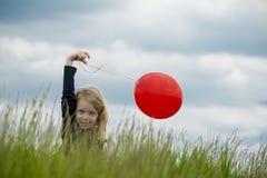 Χαμογελώντας κορίτσι με το κόκκινο μπαλόνι Στοκ εικόνες με δικαίωμα ελεύθερης χρήσης