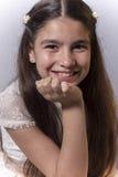 Χαμογελώντας κορίτσι με το φόρεμα κοινωνίας που στηρίζεται το χέρι της στο πηγούνι της Στοκ φωτογραφία με δικαίωμα ελεύθερης χρήσης