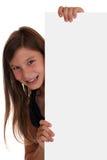 Χαμογελώντας κορίτσι που κοιτάζει πίσω από ένα κενό έμβλημα με το copyspace Στοκ Φωτογραφίες