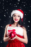 Χαμογελώντας κορίτσι που κρατά σφαίρες τις κόκκινες χριστουγεννιάτικων δέντρων Γυναίκες στο καπέλο φορεμάτων και santa ` s santa  Στοκ Εικόνα