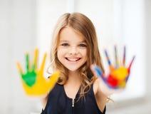 Χαμογελώντας κορίτσι που παρουσιάζει χρωματισμένα χέρια Στοκ φωτογραφία με δικαίωμα ελεύθερης χρήσης