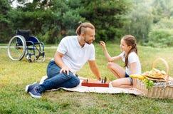 Χαμογελώντας κορίτσι που ρωτά τον πατέρα της για τους αριθμούς σκακιού Στοκ εικόνες με δικαίωμα ελεύθερης χρήσης