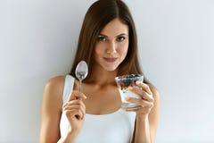 Χαμογελώντας κορίτσι που τρώει το υγιές οργανικό γιαούρτι με τα μούρα και τις βρώμες στοκ εικόνες