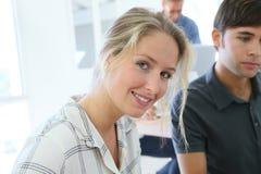 Χαμογελώντας κορίτσι σπουδαστών με τους συμμαθητές στοκ φωτογραφία