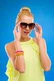 Χαμογελώντας κορίτσι στα γυαλιά ηλίου στο μπλε υπόβαθρο. Στοκ Φωτογραφία