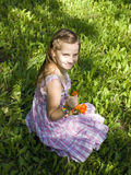 Χαμογελώντας κορίτσι στη χλόη με ένα λουλούδι Στοκ εικόνες με δικαίωμα ελεύθερης χρήσης