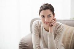 Χαμογελώντας κορίτσι στον καναπέ Στοκ φωτογραφία με δικαίωμα ελεύθερης χρήσης