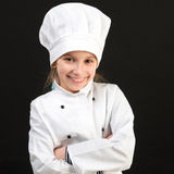 Χαμογελώντας κορίτσι στο άσπρο κοστούμι αρχιμαγείρων Στοκ εικόνα με δικαίωμα ελεύθερης χρήσης