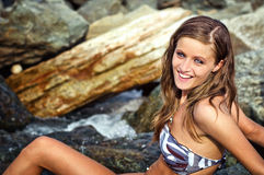 Χαμογελώντας κορίτσι brunette στο βράχο σε έναν ποταμό Στοκ Εικόνες
