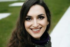 Χαμογελώντας κυρία με το καταπληκτικό καθαρό δέρμα και το γοητευτικό χαμόγελο που εξετάζει τη κάμερα Πράσινη χλόη στην ανασκόπηση Στοκ Φωτογραφία
