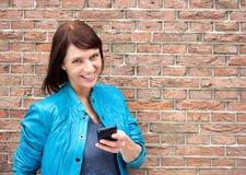 Χαμογελώντας μέση ηλικίας γυναίκα με το κινητό τηλέφωνο Στοκ Φωτογραφία