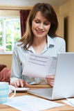 Χαμογελώντας μέση ηλικίας γυναίκα που εξετάζει τους οικιακούς πόρους χρηματοδότησης Στοκ Εικόνα