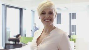 Χαμογελώντας μέση ηλικίας επιχειρησιακή γυναίκα στην αρχή φιλμ μικρού μήκους