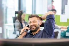 Χαμογελώντας μέσος ενήλικος επιχειρηματίας που μιλά στο τηλέφωνο στην αρχή Στοκ Φωτογραφίες