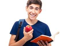 Χαμογελώντας μήλο και βιβλίο εκμετάλλευσης ανδρών σπουδαστών Στοκ φωτογραφίες με δικαίωμα ελεύθερης χρήσης