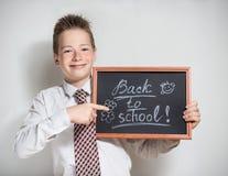 Χαμογελώντας μαθητής με τον κενό μαύρο πίνακα κιμωλίας Στοκ Εικόνες