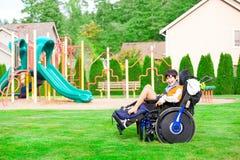 Χαμογελώντας με ειδικές ανάγκες αγόρι στην αναπηρική καρέκλα συνεδρίαση σε ένα πάρκο Στοκ φωτογραφία με δικαίωμα ελεύθερης χρήσης