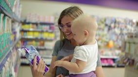 Χαμογελώντας μητέρα σε ένα τμήμα των παιδιών στην υπεραγορά που κρατά το παιδί της στα όπλα της επιλέγοντας τις πάνες απόθεμα βίντεο