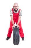 Χαμογελώντας μηχανικός που στηρίζεται σε μια νέα ρόδα αυτοκινήτων Στοκ Εικόνες