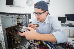 Χαμογελώντας μηχανικός υπολογιστών που εργάζεται στη σπασμένη κονσόλα με το κατσαβίδι Στοκ Εικόνες