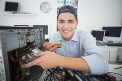 Χαμογελώντας μηχανικός υπολογιστών που εργάζεται στη σπασμένη κονσόλα με το κατσαβίδι Στοκ Φωτογραφίες