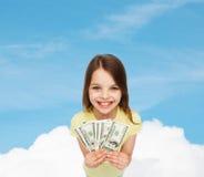 Χαμογελώντας μικρό κορίτσι με τα χρήματα μετρητών δολαρίων Στοκ εικόνα με δικαίωμα ελεύθερης χρήσης