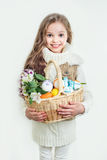 Χαμογελώντας μικρό κορίτσι με το σύνολο καλαθιών των ζωηρόχρωμων αυγών Πάσχας Στοκ Φωτογραφία