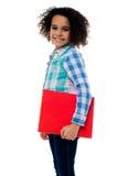 Χαμογελώντας μικρό κορίτσι που κρατά ένα σημειωματάριο Στοκ φωτογραφία με δικαίωμα ελεύθερης χρήσης