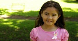 Χαμογελώντας μικρό κορίτσι που φορά το ροζ για τη συνειδητοποίηση καρκίνου του μαστού στο πάρκο απόθεμα βίντεο