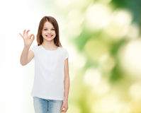 Χαμογελώντας μικρό κορίτσι στην άσπρη κενή μπλούζα Στοκ εικόνα με δικαίωμα ελεύθερης χρήσης