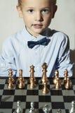 Χαμογελώντας μικρό παιδί με το σκάκι κατσίκι έξυπνο παιδί μεγαλοφυίας σκακιέρα Στοκ εικόνες με δικαίωμα ελεύθερης χρήσης