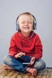 Χαμογελώντας μικρό παιδί που κλείνει τα μάτια του ακούοντας τη μουσική Στοκ φωτογραφίες με δικαίωμα ελεύθερης χρήσης