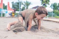 Χαμογελώντας μικρό παιδί που παίζει την άμμο Στοκ Φωτογραφία
