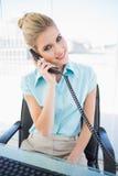 Χαμογελώντας μοντέρνη επιχειρηματίας που απαντά στο τηλέφωνο Στοκ Φωτογραφίες