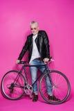 Χαμογελώντας μοντέρνο ανώτερο άτομο που φορά το σακάκι δέρματος και sunglesses που στέκεται με το ποδήλατο Στοκ φωτογραφίες με δικαίωμα ελεύθερης χρήσης