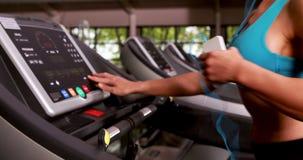Χαμογελώντας μυϊκή γυναίκα που τρέχει treadmill φιλμ μικρού μήκους