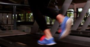 Χαμογελώντας μυϊκή γυναίκα που τρέχει treadmill απόθεμα βίντεο