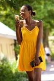 Χαμογελώντας νέα αφρικανική γυναίκα που τρώει το παγωτό υπαίθρια στοκ εικόνες