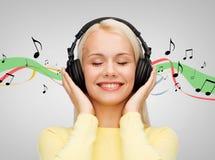 Χαμογελώντας νέα γυναίκα με τα ακουστικά Στοκ Εικόνες