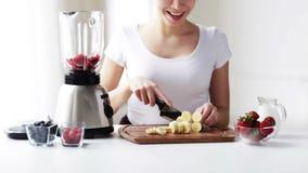 Χαμογελώντας νέα γυναίκα με την τεμαχίζοντας μπανάνα μπλέντερ φιλμ μικρού μήκους