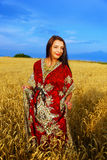 Χαμογελώντας νέα γυναίκα με τη διακοσμητική στάση φορεμάτων Στοκ φωτογραφία με δικαίωμα ελεύθερης χρήσης