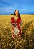 Χαμογελώντας νέα γυναίκα με τη διακοσμητική στάση φορεμάτων Στοκ Εικόνα