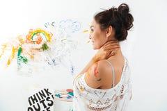 Χαμογελώντας νέα γυναίκα με τις βούρτσες στην παλέτα που στέκεται και ζωγραφική Στοκ φωτογραφία με δικαίωμα ελεύθερης χρήσης