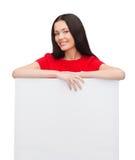 Χαμογελώντας νέα γυναίκα με τον κενό λευκό πίνακα Στοκ εικόνες με δικαίωμα ελεύθερης χρήσης